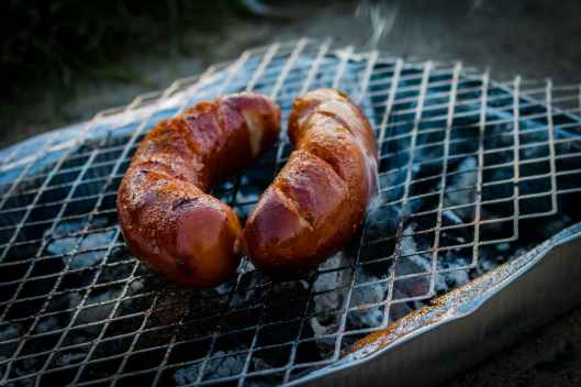 two sausages on charcoal grill